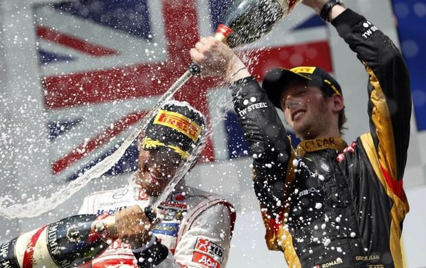 Com a bandeira da Grã-Bretanha ao fundo, Hamilton leva banho de champanhe de Grosjean (Foto: Reuters)