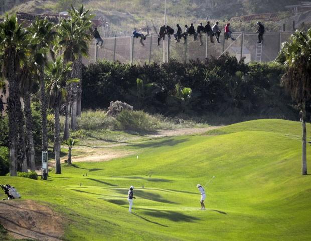 Imigrantes ilegais tentam entrar no enclave espanhol de Melilla, no norte da África, em meio a um jogo de golfe que acontecia dentro do território nesta quarta-feira (22) (Foto: Jose Palazon/Reuters)