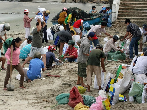 Moradores preparam sacos de areia para reforçar um dique do mar na província de Phu Yen, no Vietnã (Foto: Vietnam News Agency/AFP)