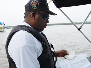 Durante abordagem, a Capitania dos Portos confere documentação da embarcação, habilitação do condutor e exige um outro documento com foto (Foto: André Resende/G1)
