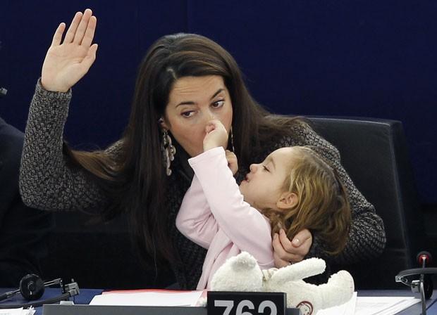 Vittoria puxa o nariz da mãe, Licia Ronzullo, durante votação no Parlamento Europeu (Foto: Vincent Kessler/Reuters)