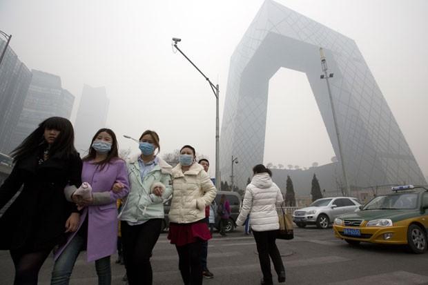 Mulheres caminham com máscara em rua de Pequim, que sofre há uma semana com a presença de uma névoa de poluição (Foto: Ng Han Guan)