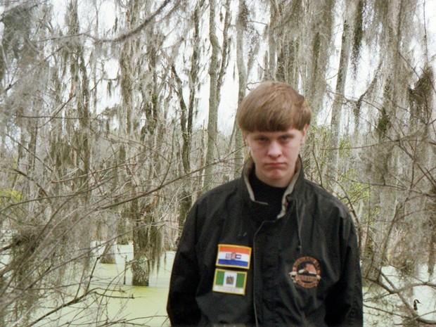 Foto do suspeito Dylann Roof em rede social mostra o jovem de 21 anos com uma jaqueta com bandeiras bordadas à esquerda: a bandeira da África do Sul na época do apartheid (topo) e a da Rodésia, antigo estado não reconhecido que instaurou um regime racista (Foto: Reprodução/Facebook/Dylann Roof)