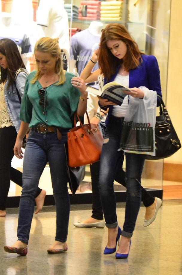 Atriz usando casual com blazer azul, jeans e blusa branca, com bolsa estruturada preta, em shopping..