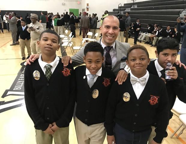 Voluntário tira foto com meninos da Dade Middle School (Foto: Reprodução Twitter @DISDPD_AChiefJR)