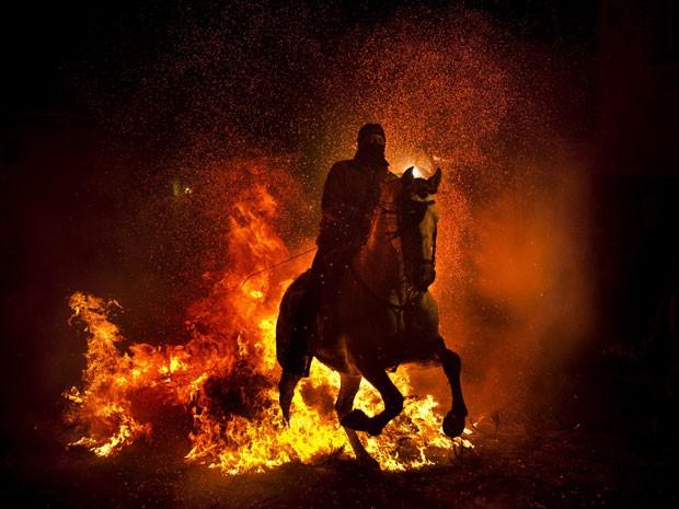 Cavaleiros montam em seus cavalos nas ruas estreitas de São Bartolomeu (Foto: Daniel Ochoa de Olza/AP)