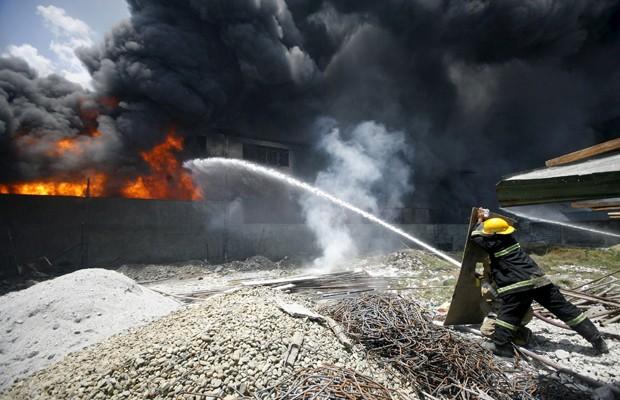 Bombeiros lutam contra fogo em fábrica da cidade de Valenzuela, em Manila, nesta quarta-feira (13) (Foto: Al Falcon/Reuters)