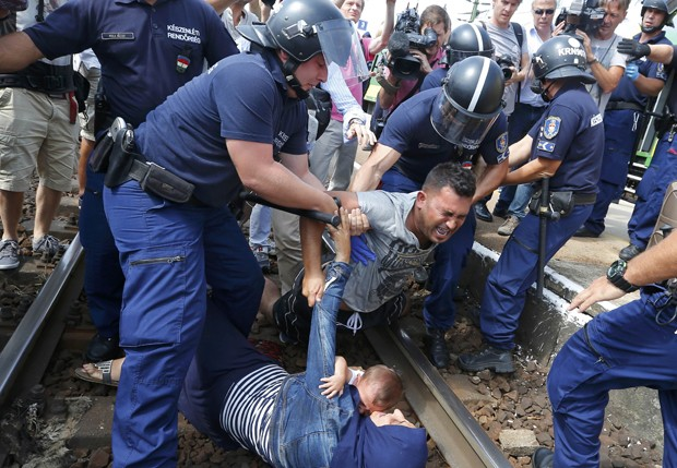Policial detém família que tentava fugir de estação de trem na cidade Bicske, na Hungria. Nesta manhã, trem foi interceptado e migrantes eram conduzidos a campo de refugiados (Foto: Laszlo Balogh/ Reuters)