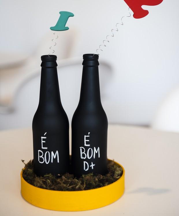 Outra maneira de utilizar garrafas na decoração: passe tinta lousa em toda superfície e, com um giz, escreva mensagens de parabéns ou o nome do bebê que está para chegar.  (Foto: Divulgação/Sandra Pagano)
