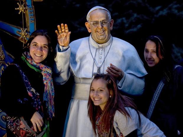 Fiéis posam ao lado da estátua do papa Francisco criada pelo artista Fernando Pugliese (Foto: Alejandro Pagni / AFP)