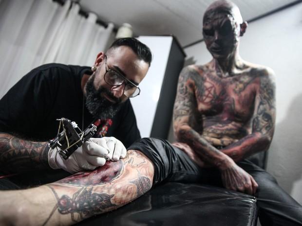 Jhon Tattoo está desenhando uma faratura exposta na perna de Coveiro Maldito (Foto: Fábio Tito/G1)