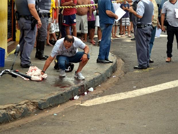 Irmão limpa o sangue de vítima na Rua Demétrio Chaguri, no Quintino, em Ribeirão Preto (Foto: Eduardo Guidini/ G1)