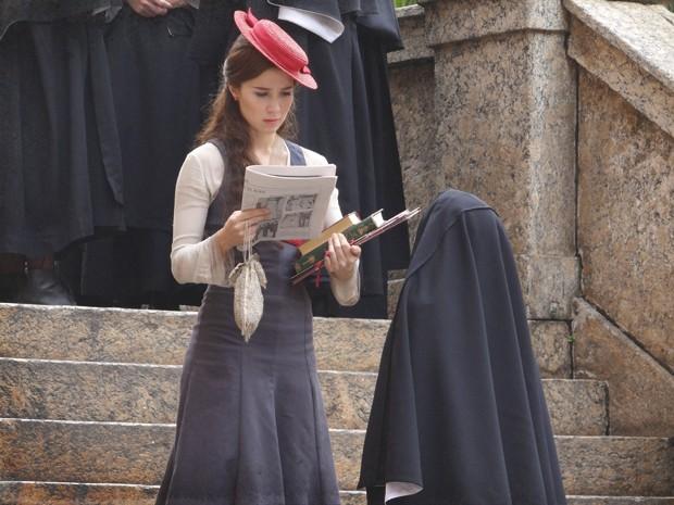 Laura vê sua foto no jornal (Foto: Lado a Lado/TV Globo)
