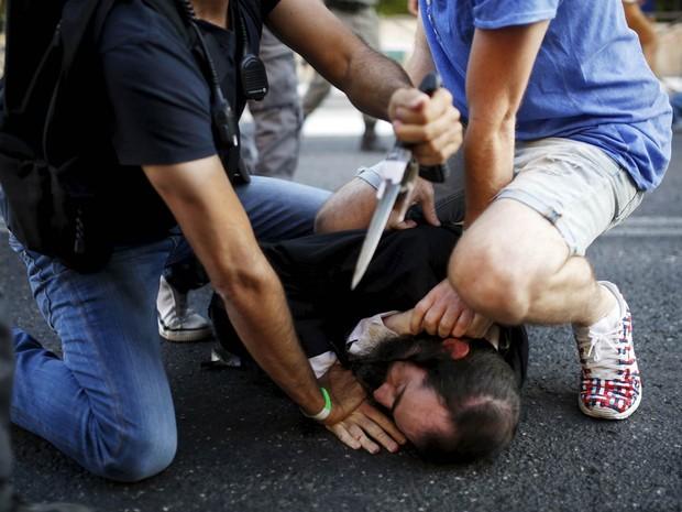 Pessoas desarmam o judeu ultraortodoxo que atacou participantes da parada gay com uma faca em Jerusalém, Israel. Seis pessoas ficaram feridas no ataque (Foto: Amir Cohen/Reuters)