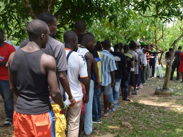 Imigrantes formam fila para receber marmita  (Foto: Aline Nascimento/G1)