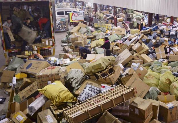Funcionários de empresa de logística empilham compras feitas no Dia do Solteiro na China (Foto: Reuters)