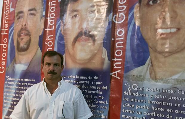 O espião cubano Fernando Gonzalez posa em frente a cartaz mostrando o rosto de outros três espiões. Os três serão soltos pelo governo americano após novo acordo entre EUA e Cuba (Foto: Franklin Reyes/AP)