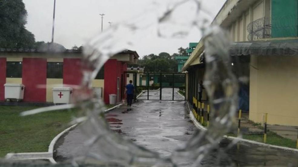 Visão por meio de buraco feito por tiro em sala da direção do Compaj (Foto: Felipe Souza/BBC Brasil)