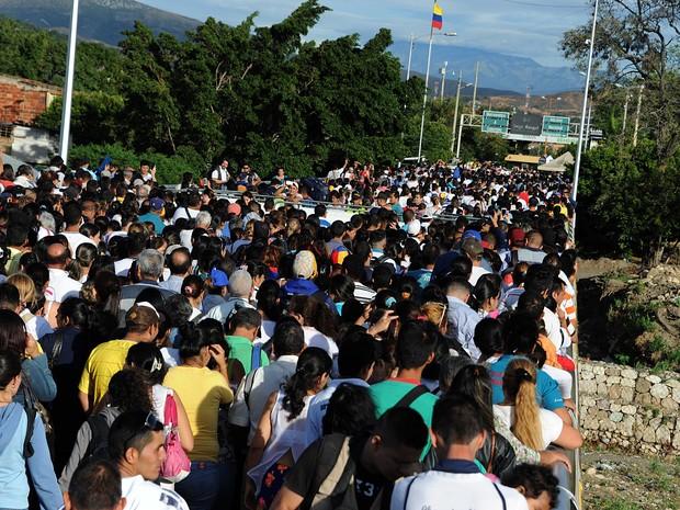 Multidão atravessa ponte rumo a Cucutá, na fronteira entre Venezuela e Colômbia, neste domingo (10) (Foto: GEORGE CASTELLANOS/AFP)