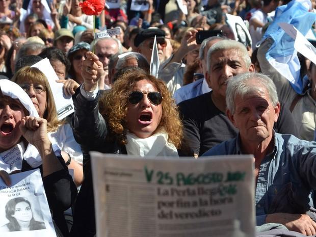 Manifestantes protestam do lado de fora da Corte Federal de Córdoba, na Argentina, na quinta (25), durante julgamento de militares envolvidos em crimes na ditadura (Foto: Laura Lescano/TELAM AFP/AFP)