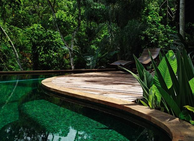Dentro da piscina, o banco segue o curso do deque de madeira de demolição, do Mercador da Serra, e ainda serve de escada. Uma combinação de mosaicos de vidro de 2 x 2 cm, em vários tons de verde, da coleção Transições, da Vidrotil, reveste o seu interior (Foto: Casa e Jardim)