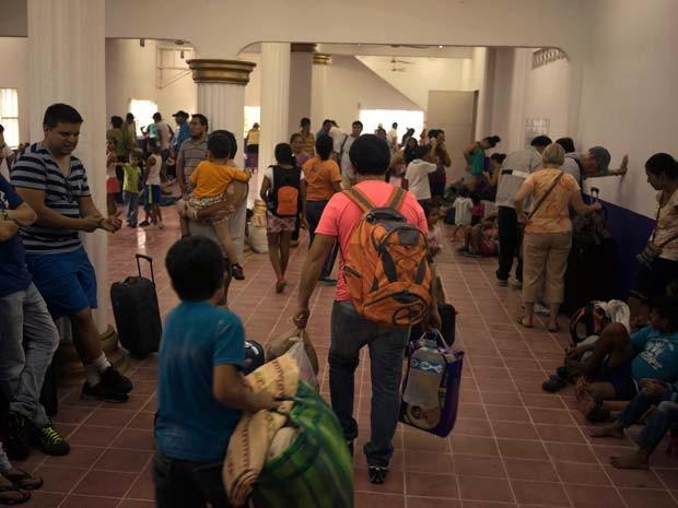 Famílias chegam a albergue habilitado para esperar a chegada do furacão Patricia em Puerto Vallarta, no México (Foto: AP Photo/Cesar Rodriguez)