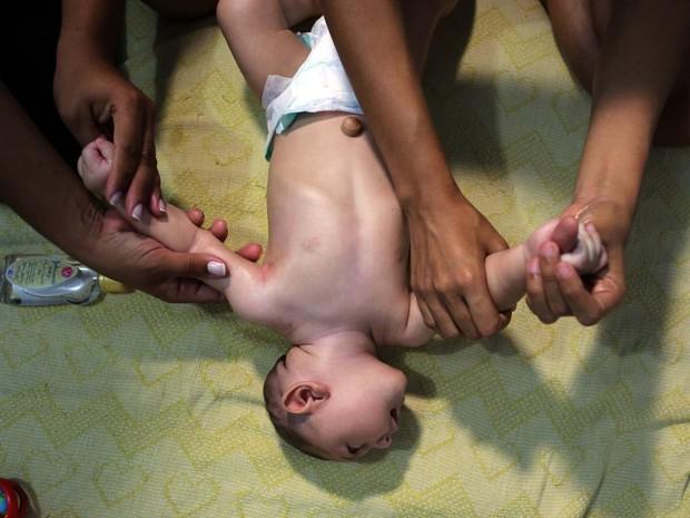 Terapeuta ensina Daniele Santos a fazer a manssagem shantala em seu filho, que nasceu com microcefalia (Foto: REUTERS/Paulo Whitaker )