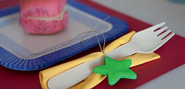 O jogo americano é de papel sulfite colorido. Uma estrelinha de porcelana fria incrementa o garfo descartável (Foto: Lufe Gomes)