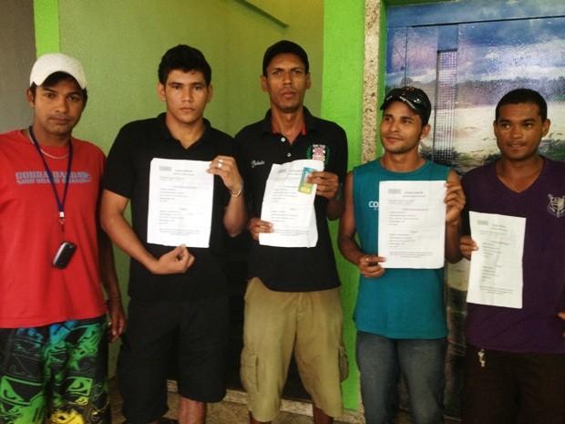 Trabalhadores mostram documento fornecido pela construtora para retirar as passagens junto às empresas de transporte (Foto: Vanessa Vasconcelos/G1)