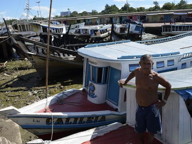 Pescador Severino Santana divide espaço com barco incendiado no Amapá (Foto: John Pacheco/G1)