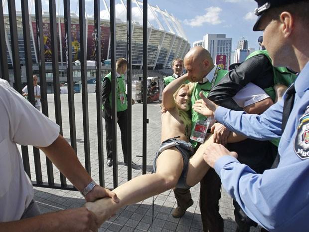 Seguranças precisaram carregar umas das manifestantes que protestava no local em que será disputada a partida de futebol entre Inglaterra e Itália, pela Eurocopa (Foto: Gleb Garanich/Reuters)