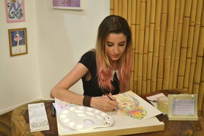Camila costuma ilustrar rostos e corpos femininos, penas de aquarela, ícones pops, flores, animais e mensagens (Foto: Luana Daubian)