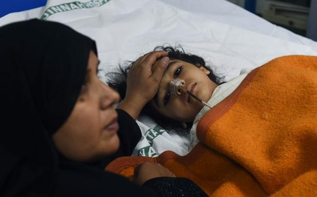 Mãe acompanha em hospital filha que ficou ferida no atentado de domingo (Foto: Farooq Naeem/AFP)