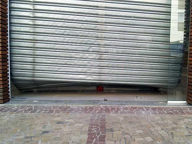 Loja no bairro Cambuí, em Campinas, com a porta danificada pela gangue da marcha à ré (Foto: Marcello Carvalho/G1)