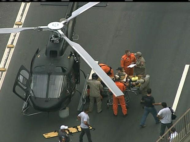 Vítima, na maca, é colocada em helicóptero para ser levada a hospital (Foto: Reprodução / TV Globo)