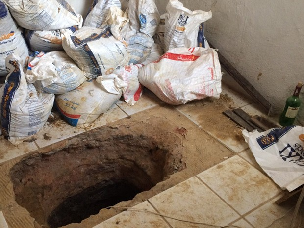 Buraco foi encontrado em casa ao lado do presídio (Foto: Thays Estarque/G1)