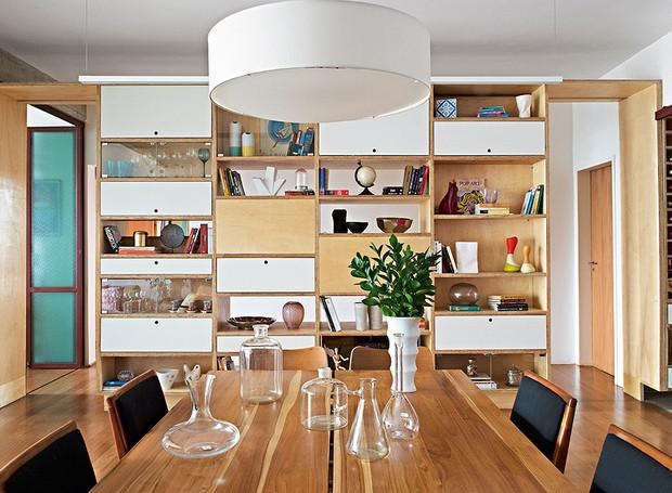 A estante é o destaque da área social do projeto do escritório Apiacás Arquitetos. Ela começa na área de serviço e termina na sala de jantar, onde guarda taças, livros e objetos de design (Foto: Marcelo Magnani/Casa e Jardim)