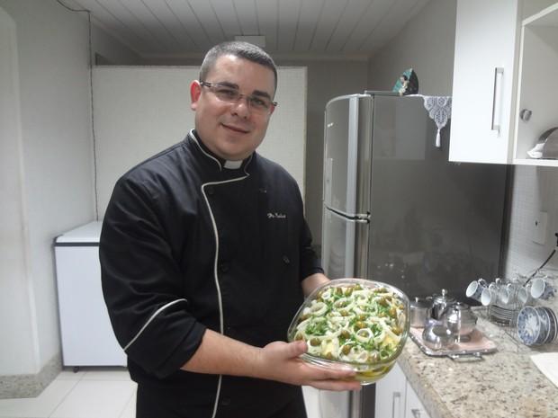 Padre Carlos Augusto mostra a receita de bacalhau a Gomes de Sá (Foto: Natália Mello / G1)