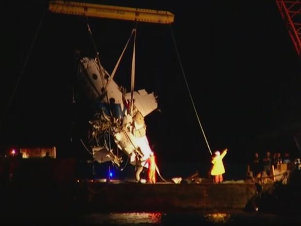 Destroços do avião são colocados na balsa após serem içados em Paraty na noite deste domingo (22) (Foto: Reprodução / TV Globo)