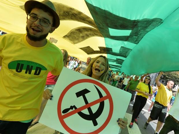 Manifestantes na Avenida Paulista seguram cartaz anti-socialismo durante ato deste domingo (16) (Foto: AFP PHOTO/NELSON ALMEIDA)