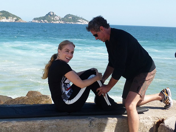 Angélica fazendo abdominal na praia com ator (Foto: Estrelas/TV Globo)