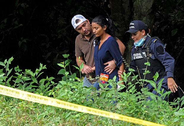 Irmã de María José Alvarado e Sofia Trinidad é amparada por policiais depois de reconhecer os corpos das famliliares (Foto: Orlando Sierra/AFP)