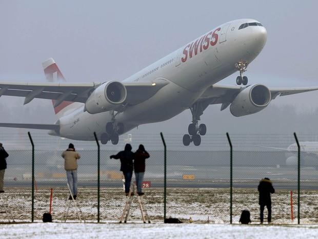 Pessoas fotografam a decolagem de um avião Airbus da Swiss em Zurique, na Suíça (Foto: Arnd Wiegmann/Reuters)