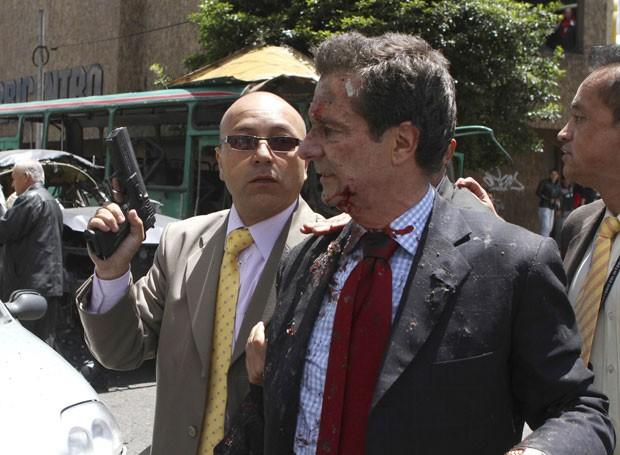 Ferido em explosão, ex-ministro é acompanhado por seguranças (Foto: Fredy Builes/Reuters)