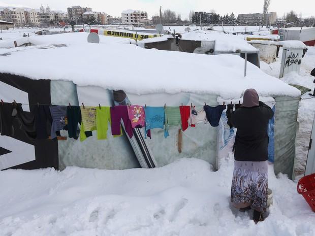 Uma mulher síria pendura roupas no varal do lado de fora de sua barraca coberta por neve em um campo de refugiados em Zahlé, no leste do Líbano. A neve na região já matou pelo menos dois refugiados (Foto: Hussein Malla/AP)