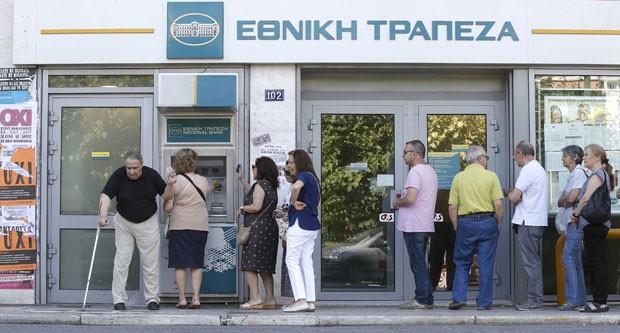 Cartazes pela vitória do 'não' em referendo são vistos enquanto as pessoas fazem fila em um caixa eletrônico para retirar dinheiro em Atenas, na Grécia, neste domingo (5) (Foto: Christian Hartmann/Reuters)