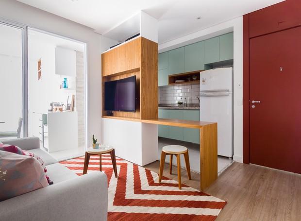 LIVING | O piso de vinílico foi escolhido pela praticidade de limpeza. A porta laqueada com tom de ferrugem foi uma das últimas decisões de decoração do lar e veio para trazer uma cor vibrante ao imóvel  (Foto: Andre Araujo (ATA Photograph)/Divulgação)