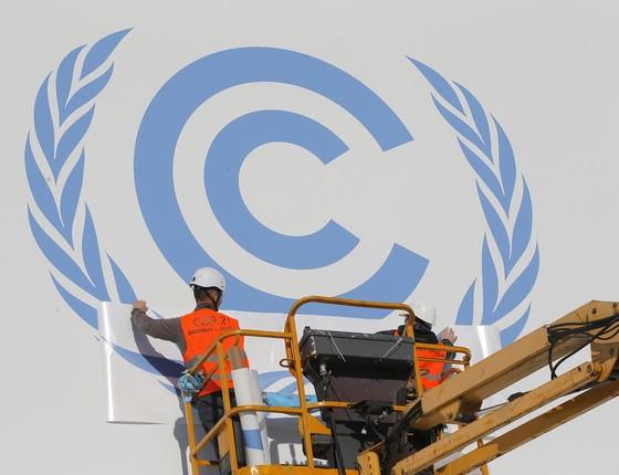 Trabalhadores instalam logo da Conferência do Clima no Le Bourget, em Paris (Foto: Christophe Ena/AP)