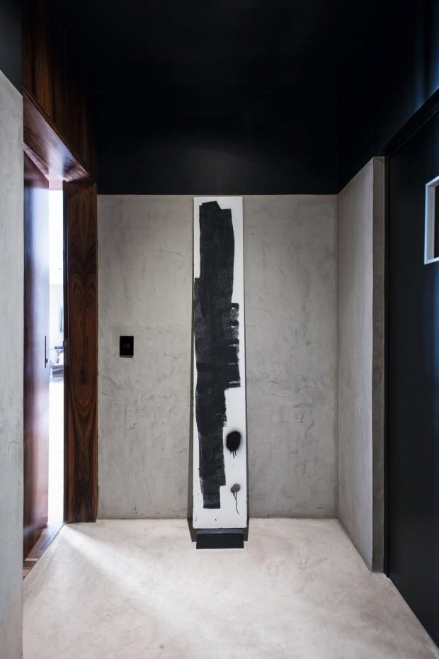 Hall de entrada. Quem sai do elevador pode observar a tela assinada por Gabriel Carracedo, dono do apê, no ambiente em preto e cinza com porta de pau-ferro (Foto: André Klotz / Editora Globo)