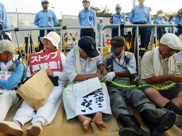 Grupo contrário ao uso de energia nuclear protesta na frente da central atômica de Sendai. Alguns se acorrentaram (Foto: Jiji Press / via AFP Photo)